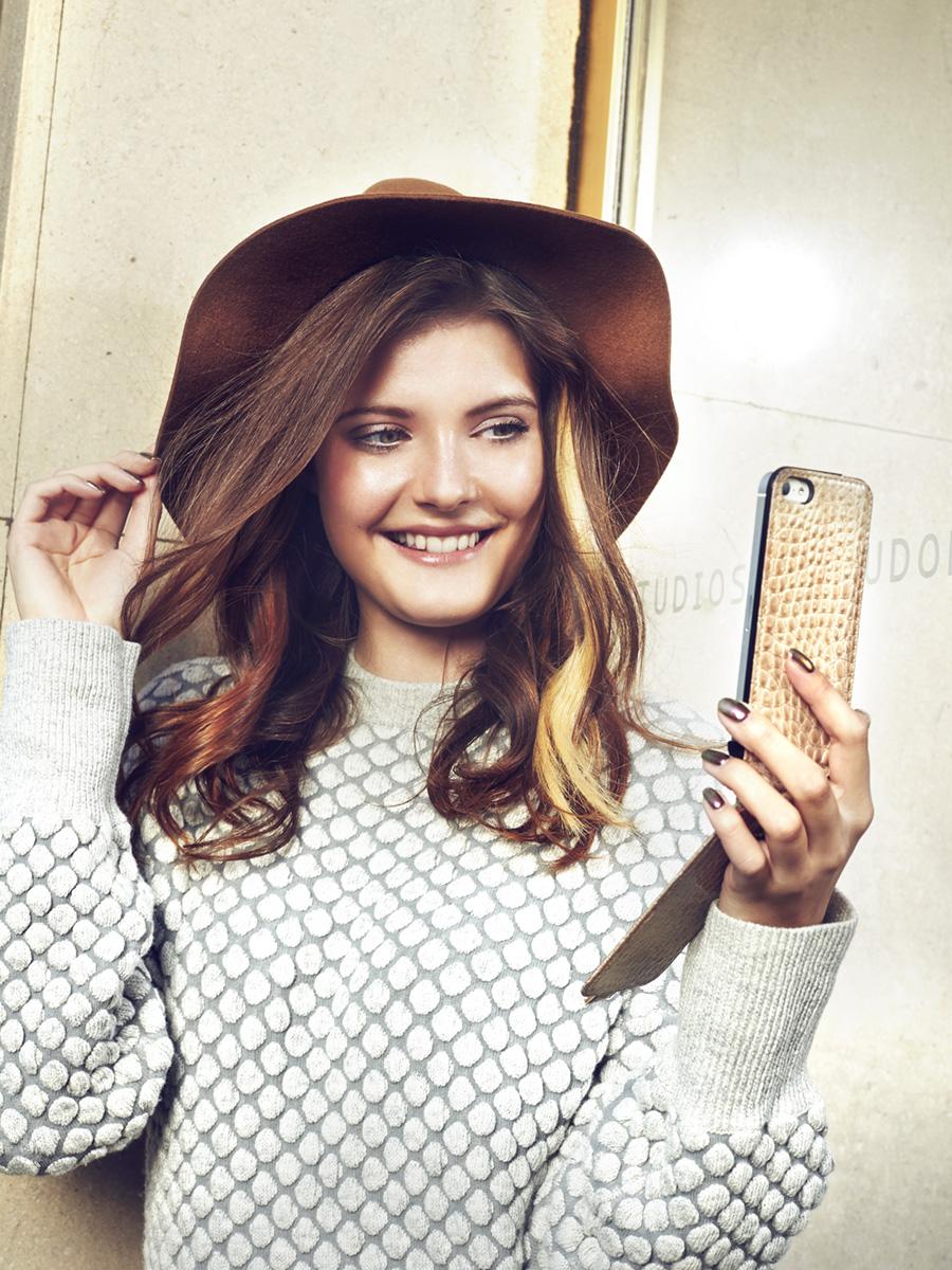 Model mit Hut macht Selfie mit Smartphone