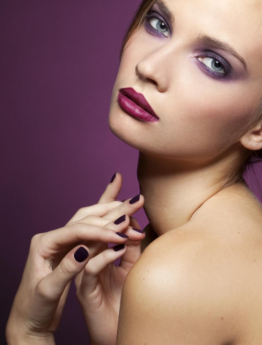 Model Portrait lila Nägel, Lippenstift und Lidschatten vor lila Hintergrund