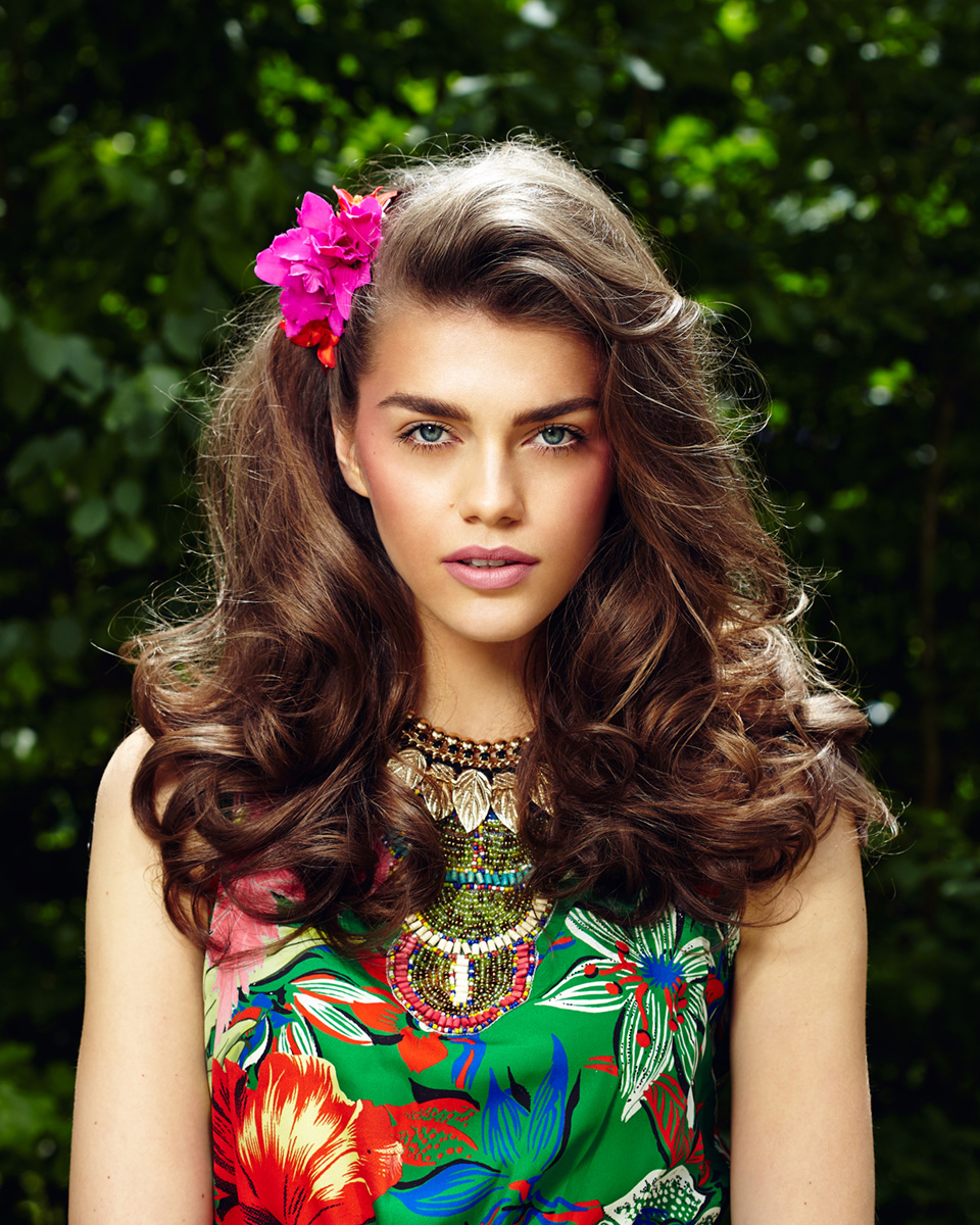 Brünettes Model mit Blumenprint Kleid und rosa Blume im Haar
