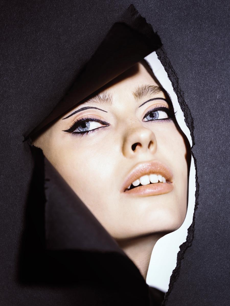Model schaut durch schwarze Papierwand mit geometrischem Eyeliner