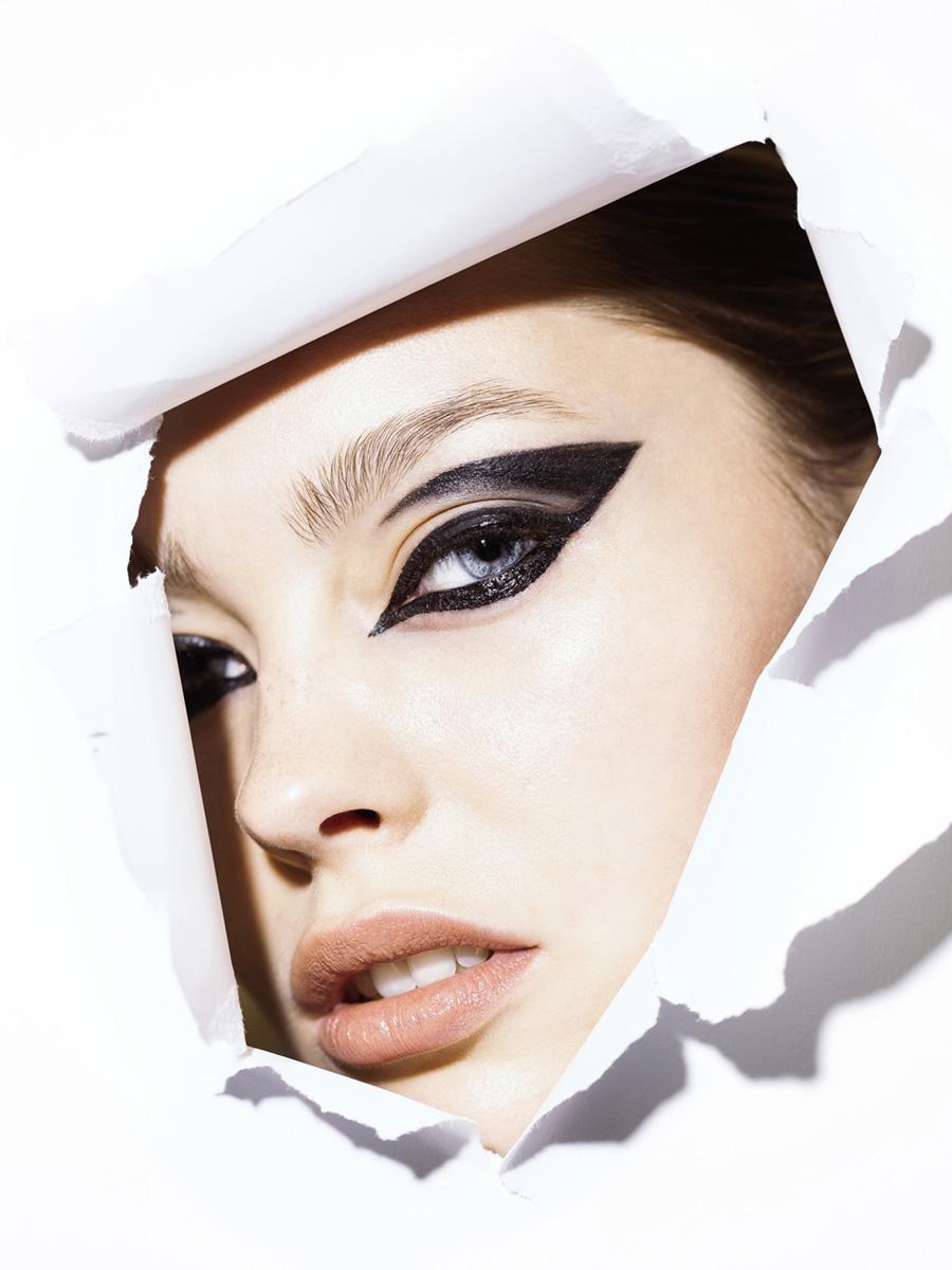 Model schaut durch weiße Papierwand mit Katzenaugen Eyeliner
