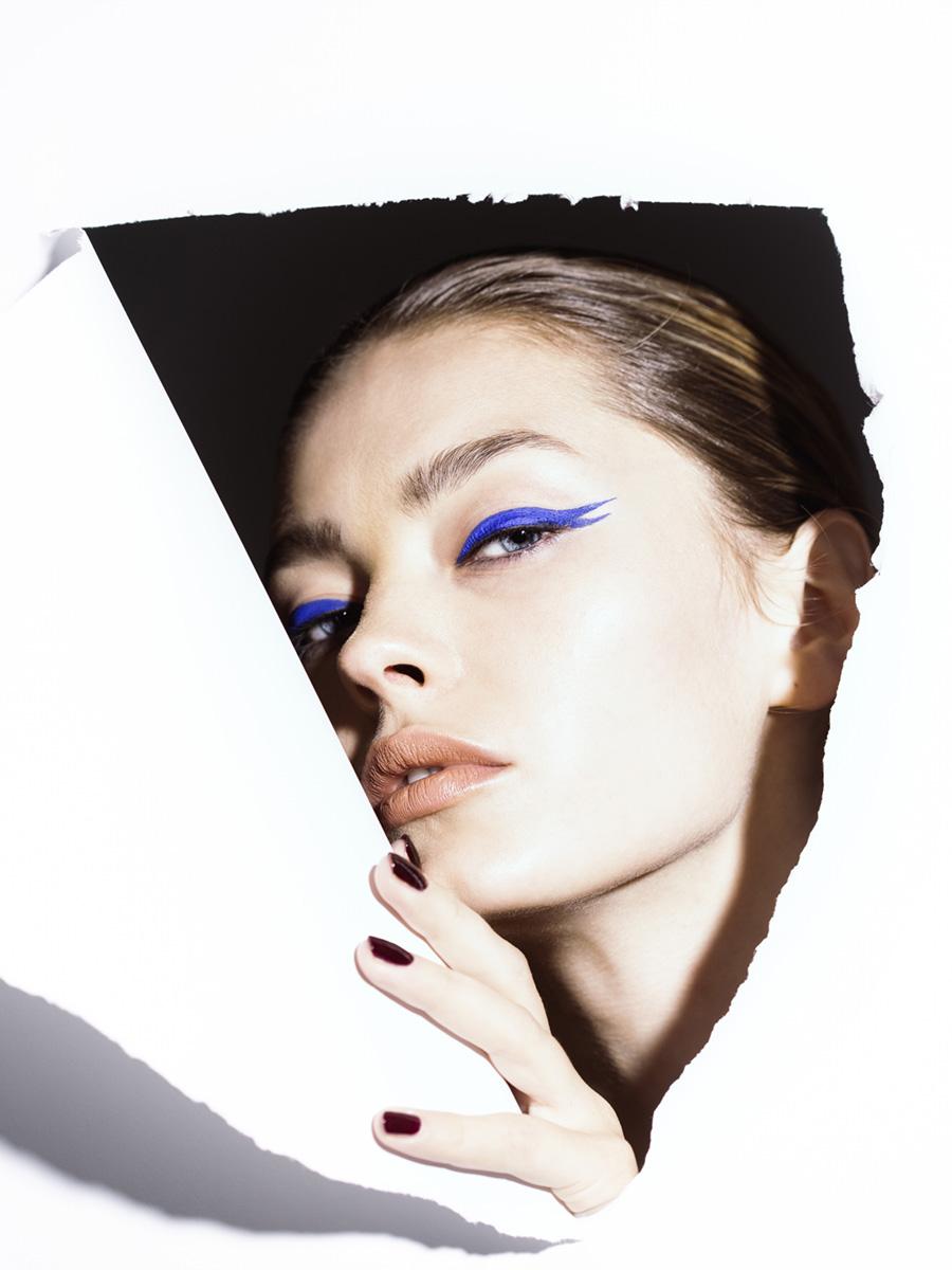 Model schaut durch weiße Papierwand mit speziell geschminkten Augen