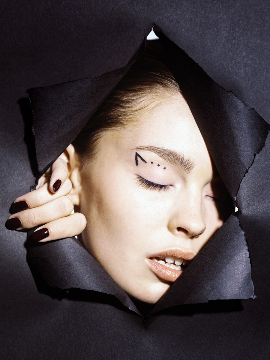 Model schaut durch schwarze Papierwand mit geometrisch geschminkten Augen