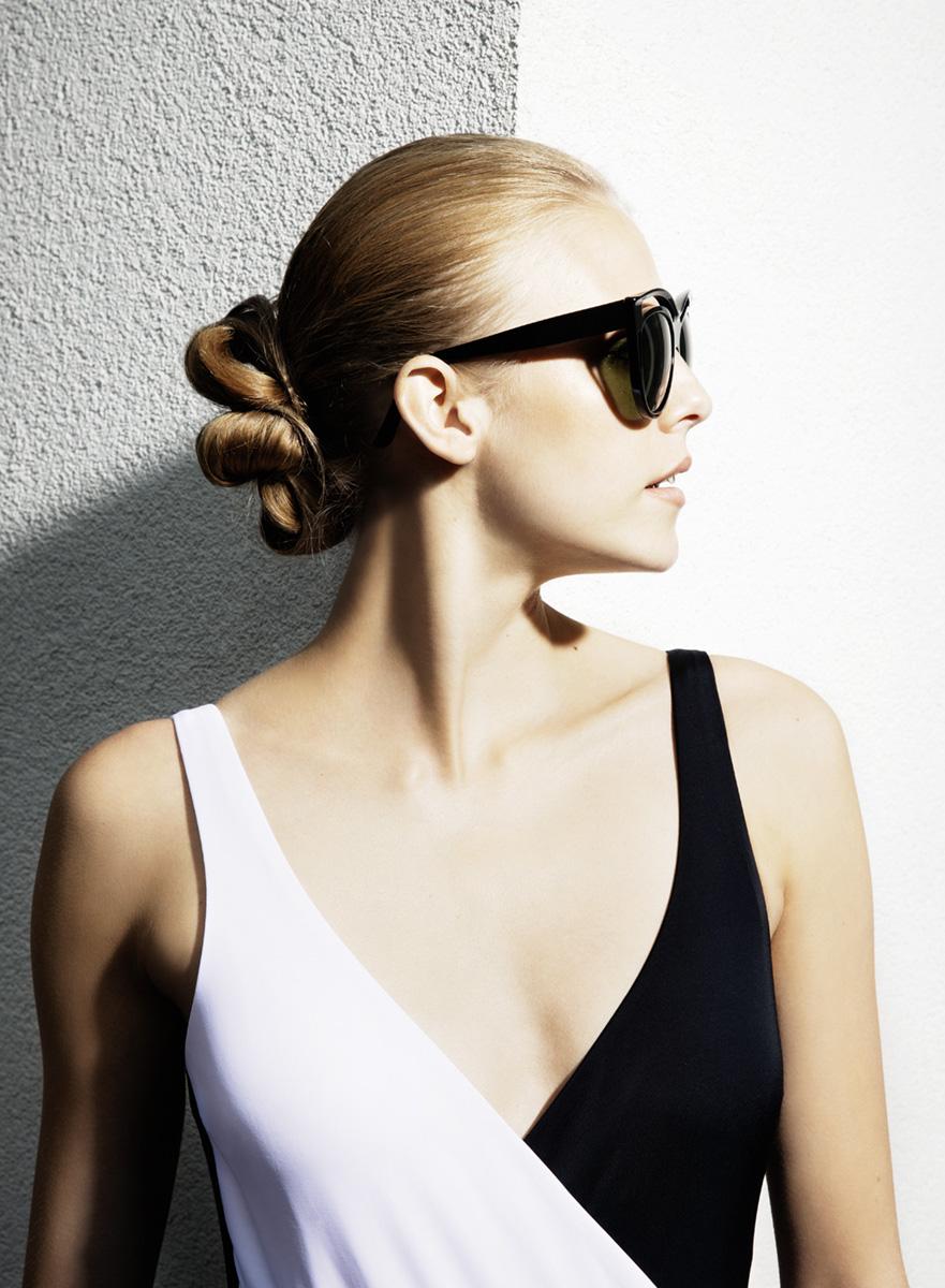 Model seitlich im schwarz weissen Badeanzug präsentiert eine Sonnenbrille