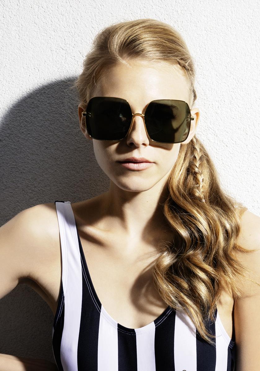 Model Portrait im schwarz weissen Badeanzug präsentiert eine Sonnenbrille