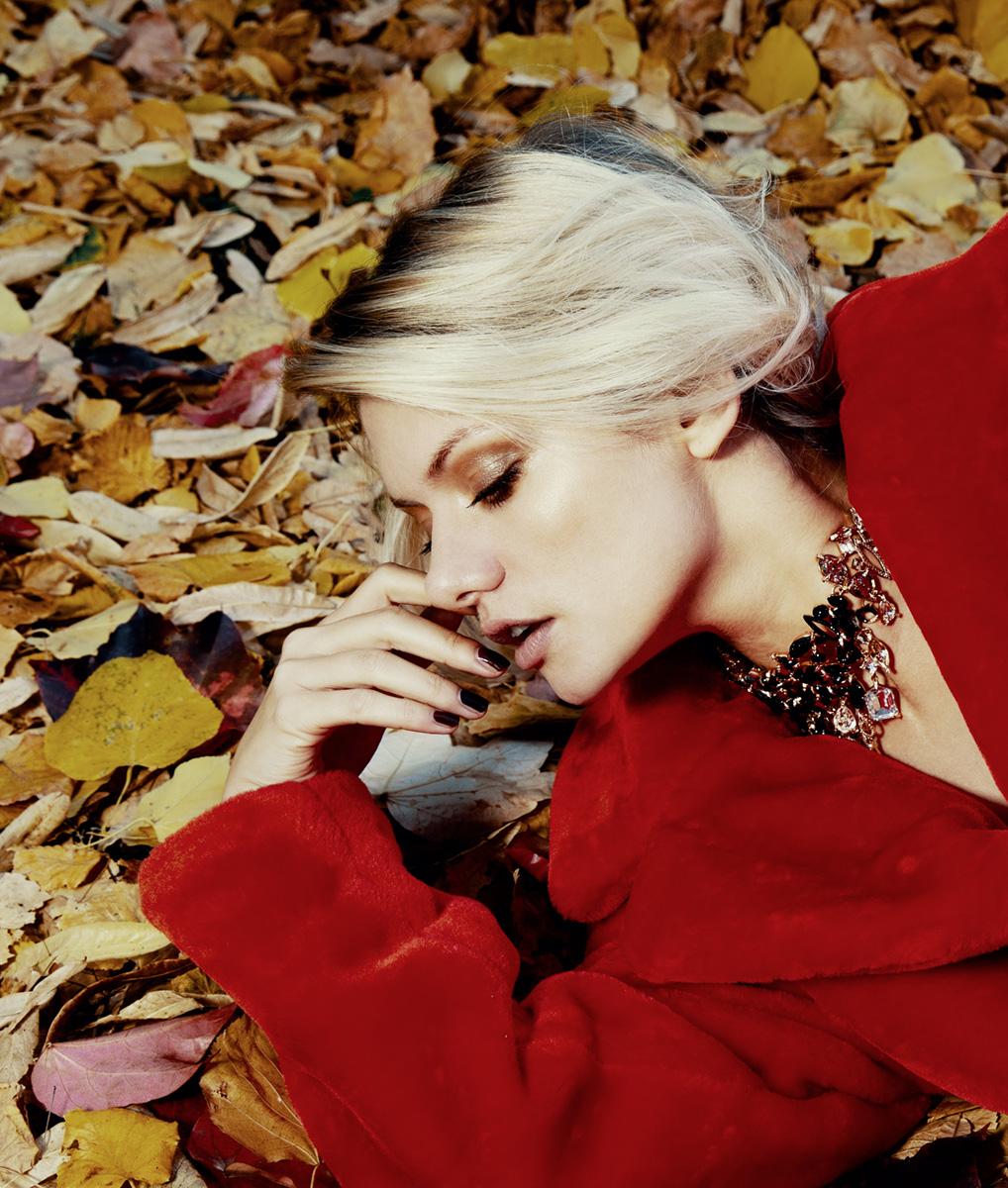 Model im roten Pelzmantel liegt vor Laub
