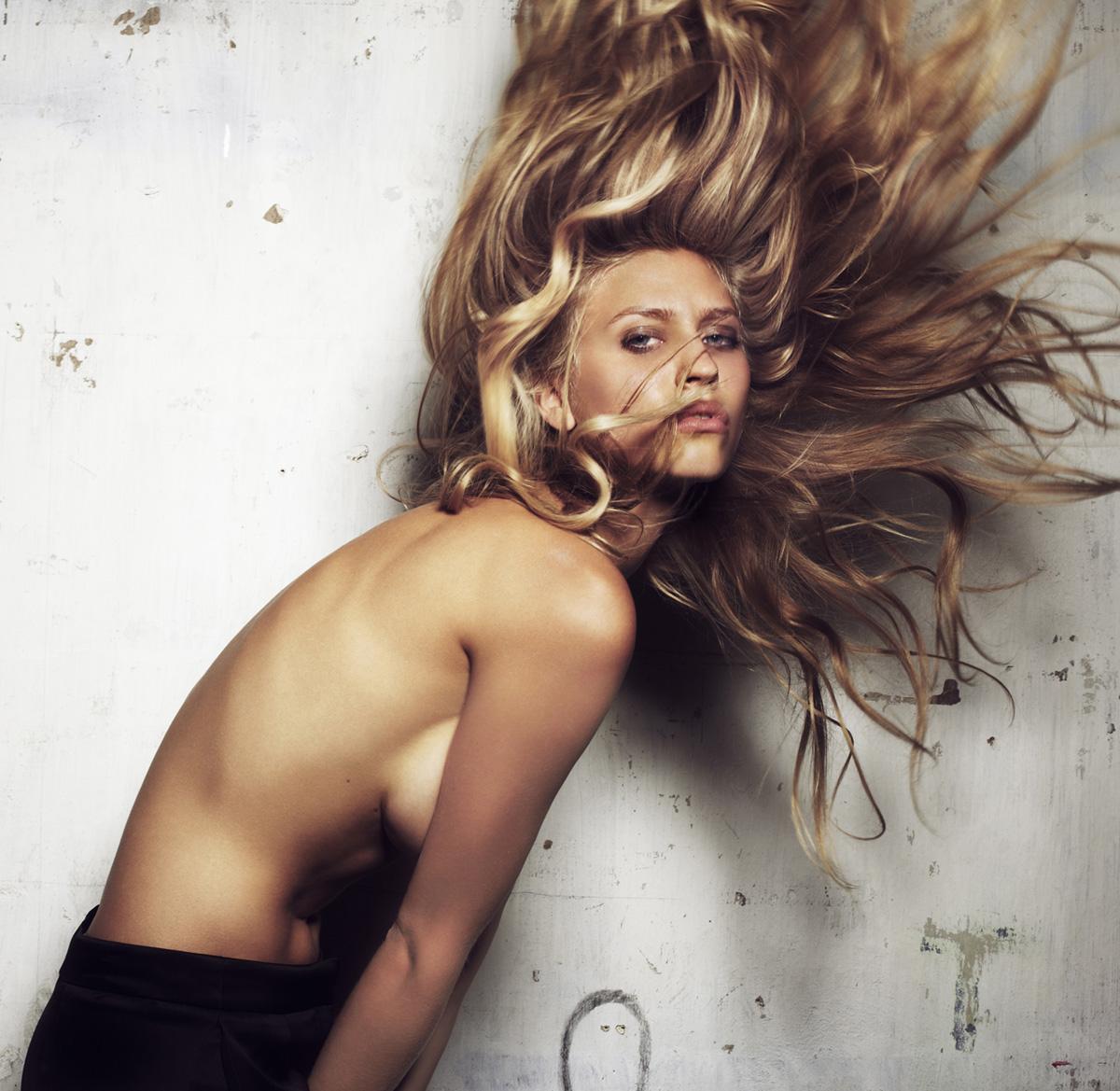 Model oben ohne wirft Haare in die Luft