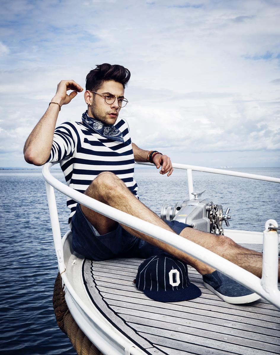 Mann im gestreiften Maritim Look sitzt auf Segelboot