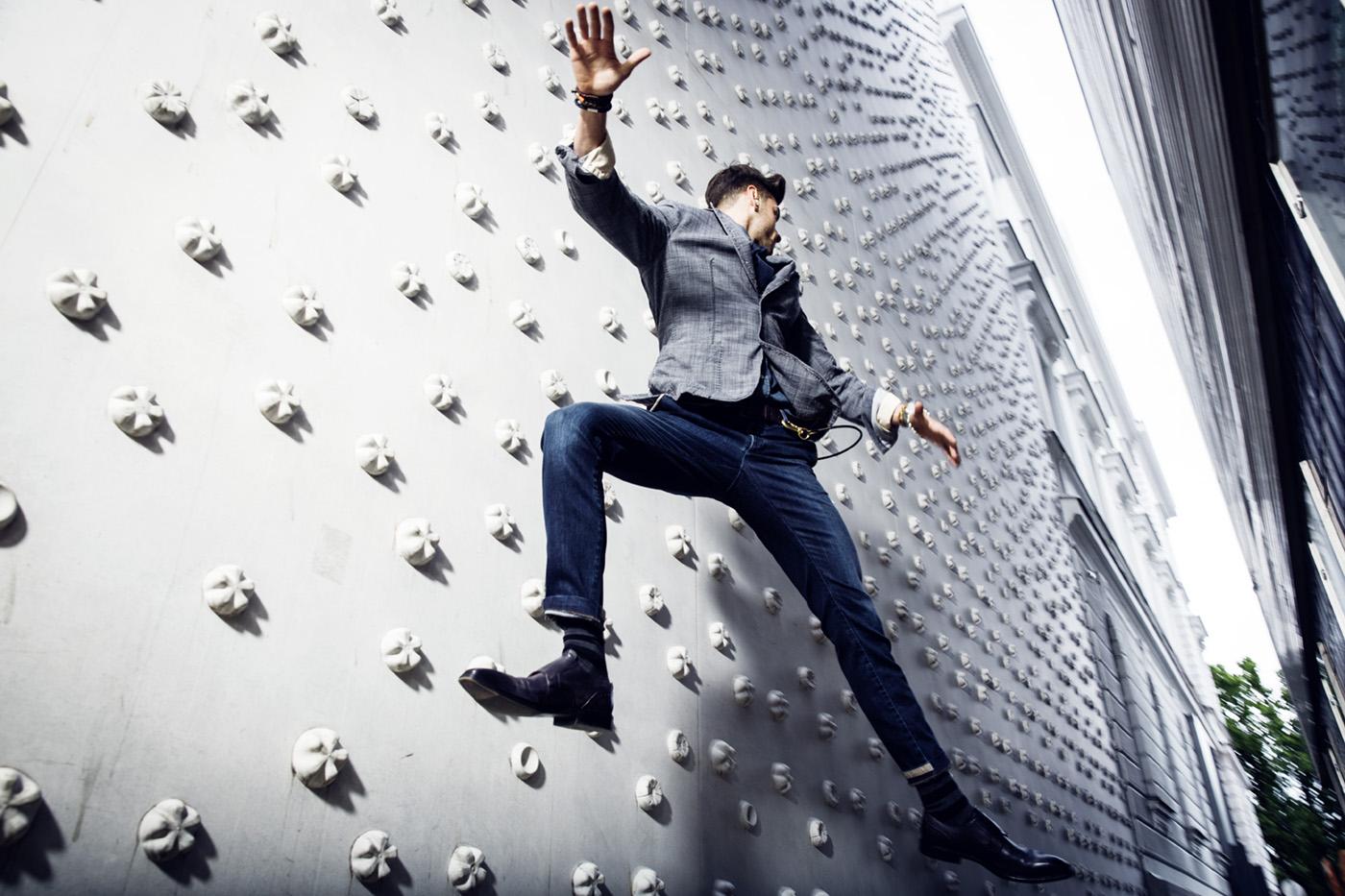 Model in Jeans und grauem Blazer vor weißer Kletterwand